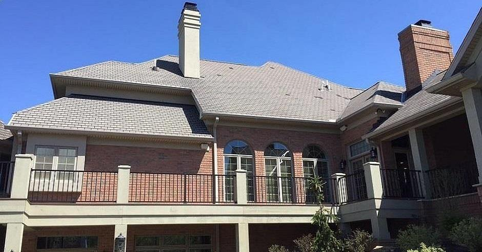 Ground view of the back of a house with a new asphalt shingle roof