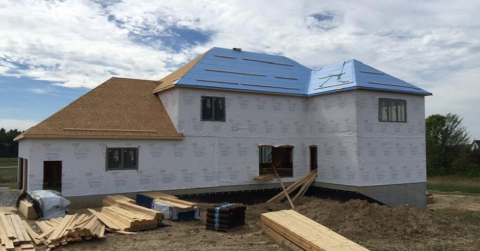Ice and water membrane being installed on a roof deck