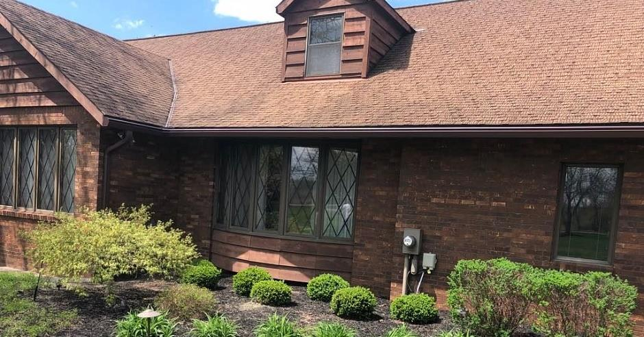 Front view of a house with new brown K-Guard Leaf Free Gutters and brick siding